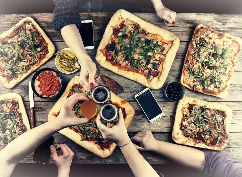 Eating Concept. Enjoying dinner with friends, Top view of group of people having dinner together while sitting at the rustic woode stock images