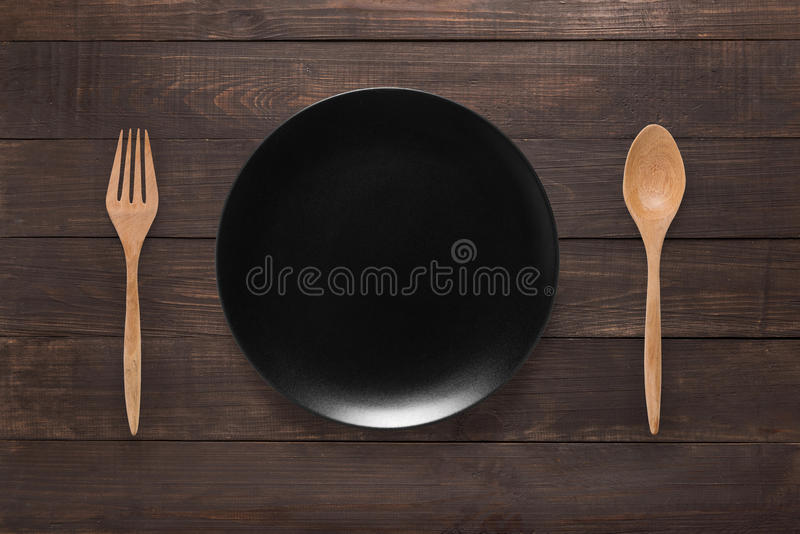Eating concept. Spoon, fork and black dish on the wooden background stock photo
