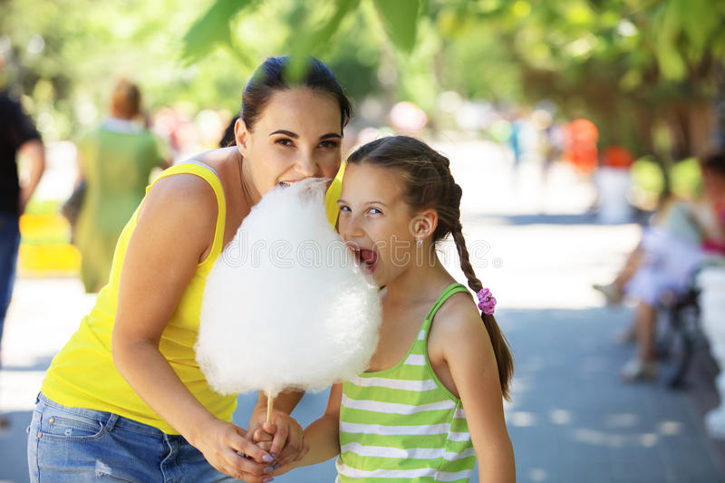 Eating cotton candy. Child eats cotton candy with mom in city street royalty free stock photo