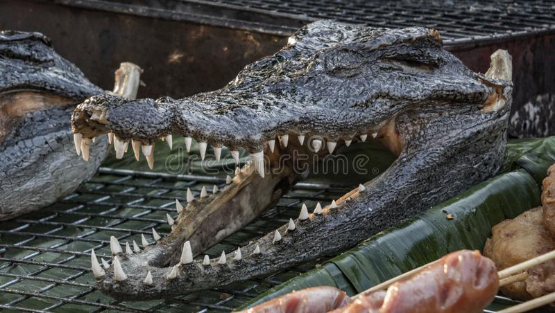 Eating crocodile. Local food market in Bangkok, Thailand. Grill, grilled, barbecue royalty free stock photos
