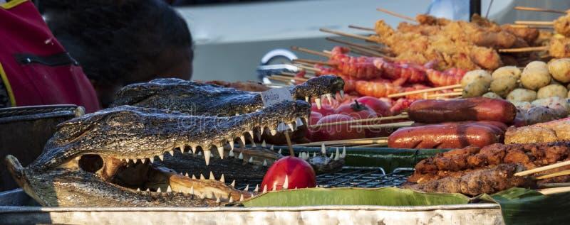 Eating crocodile. Local food market in bangkok, thailand. culture, foodmarket, marketstal, display, animal, cruelty, asia, cuisine, crocodilefarm, aligator royalty free stock image