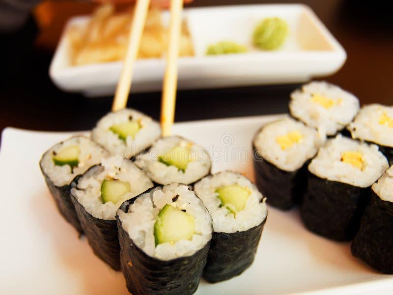 Eating cucumber Sushi. royalty free stock photography
