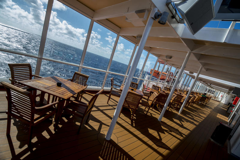 Eating deck of a cruise ship on angle. Eating wood tables and chairs line the gallery on the cruis ship royalty free stock photos