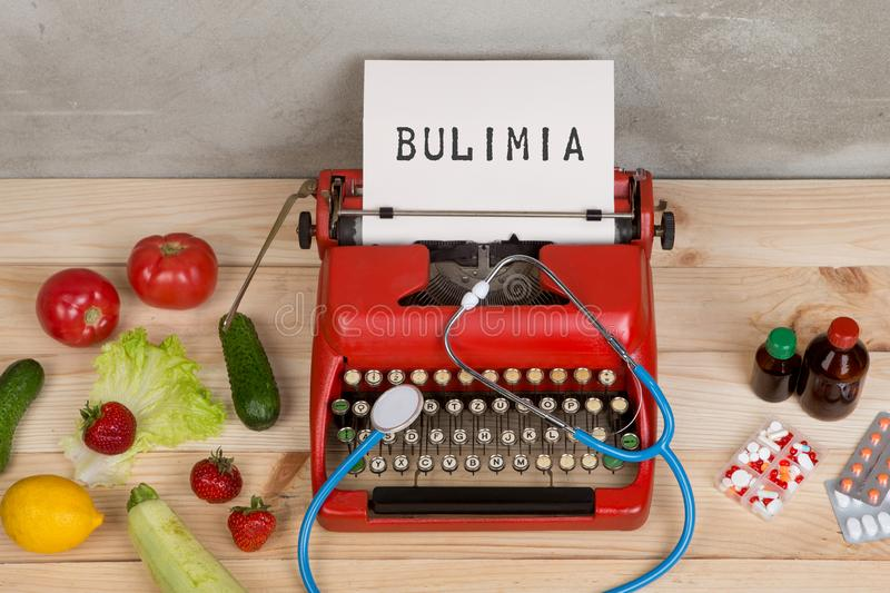 Eating disorder concept - typewriter with text Bulimia, stethoscope, vegetables, fruits and berries, tablets and pills. On wooden table, food, hunger, healthy stock image