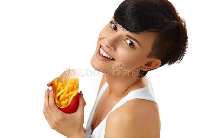 Eating Fast Food. Girl Eating French Fries. Nutrition. Lifestyle. Eating Fast Food. Portrait Of Happy Caucasian Woman Eating French Fries Chips ( Fried Potatoes royalty free stock image