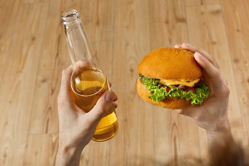 Eating Fast Food. Hamburger And Beer. Dinner At Restaurant. Nutrition. Eating Fast Food. Closeup Of Man's Hands Holding Classic American Hamburger And Bottle Of royalty free stock photos