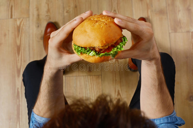 Eating Fast Food. Hands Holding Hamburger. Point Of View. Nutrition. Eating Fast Food. Close Up Of Man's Hands Holding Delicious Classic American Hamburger royalty free stock photos