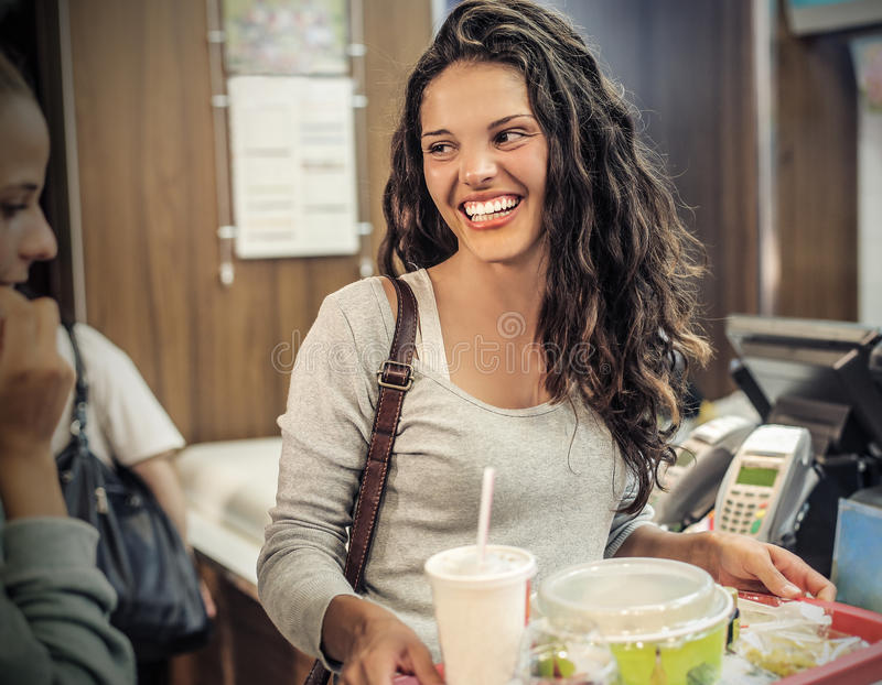 Eating at a fast food restaurant. A girl eating at a fast food restaurant stock photography