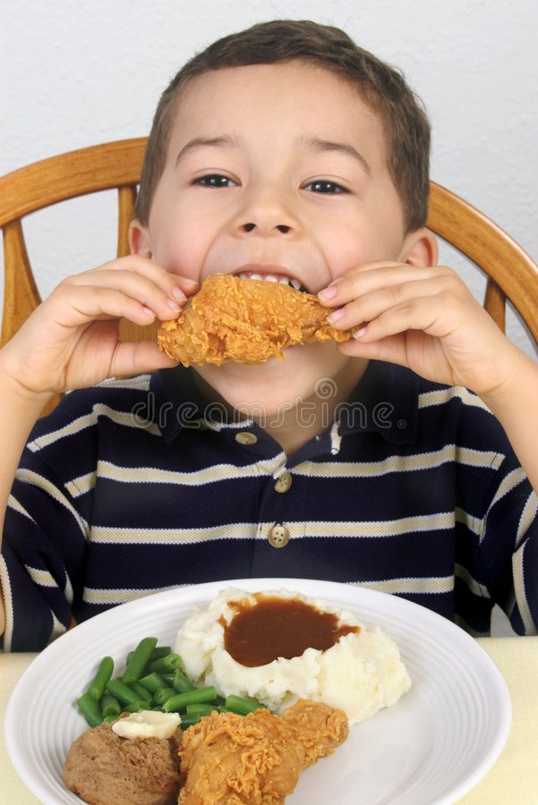 Eating fried chicken 5 years old. A five-year-old boy eating fried chicken royalty free stock image