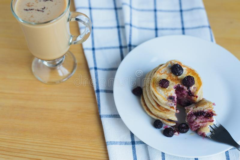 Eating of fritter or pancakes with blackberry with fork on white dish and coffee royalty free stock photos