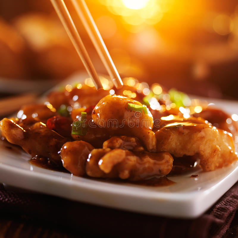 Eating general tso's chicken with chopsticks. With orange lens flare in background royalty free stock image