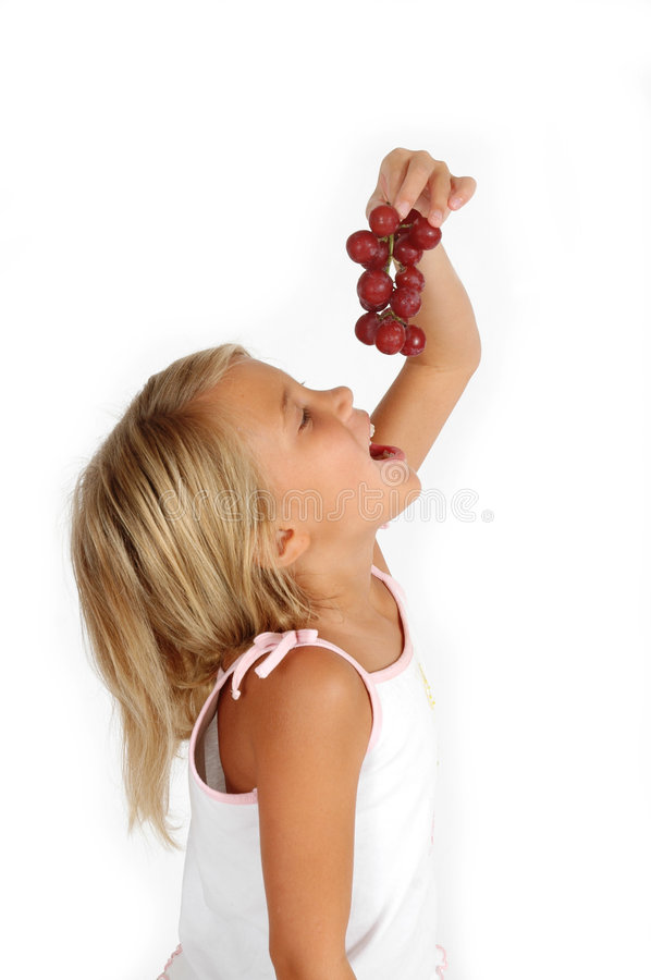 Eating Grapes. Dropping grapes into her mouth from above. Little girl eats healthy friut and chooses better snacks than sugar or candy royalty free stock photography
