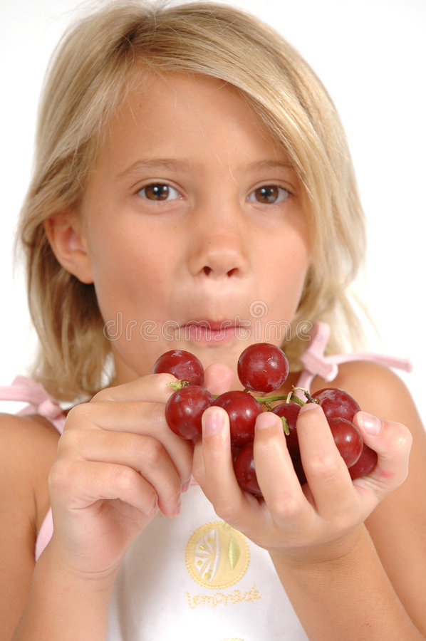Eating Grapes. Little girl holds out hand to tempt you to eat grapes. Little child hods out healthy food choice stock photo