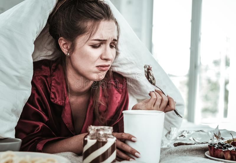 Depressed woman eating a lot of sweets royalty free stock photo