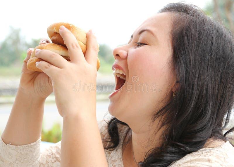 Eating hamburger. Closeup image of asian woman eating hamburger at coffeeshop royalty free stock photo