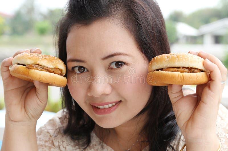 Eating hamburger. Closeup image of asian woman eating hamburger at coffeeshop royalty free stock photos