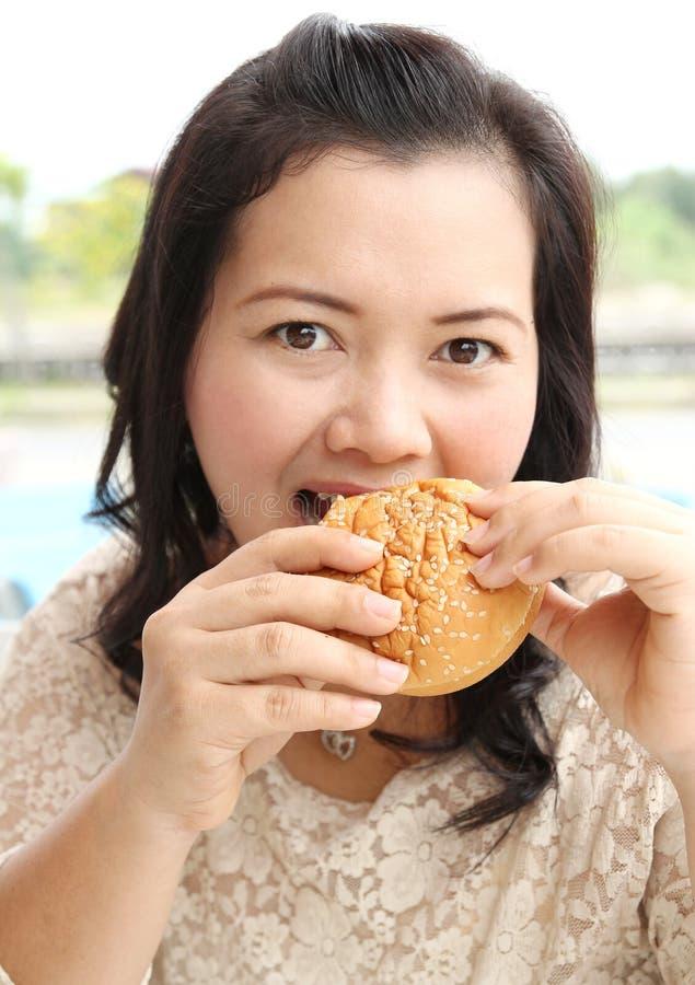 Eating hamburger. Closeup image of asian woman eating hamburger at coffeeshop stock photos