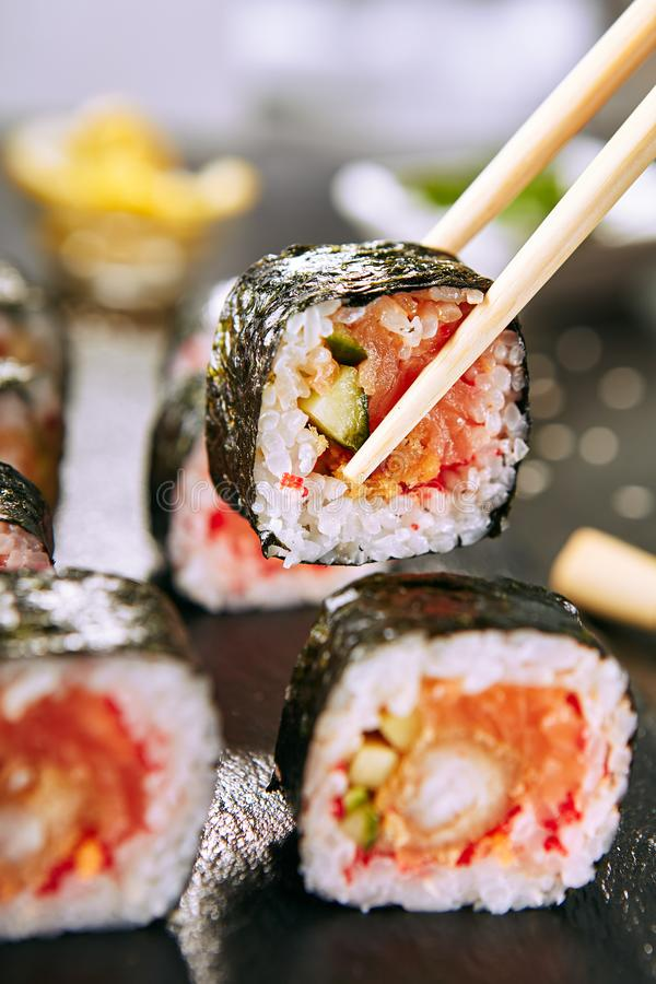 Eating Hot Spicy Uramaki Sushi Rolls in Japanese Restaurant Closeup stock photos