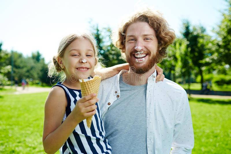 Eating ice-cream. Happy girl and her father eating ice-cream on hot sunny day in park royalty free stock photo