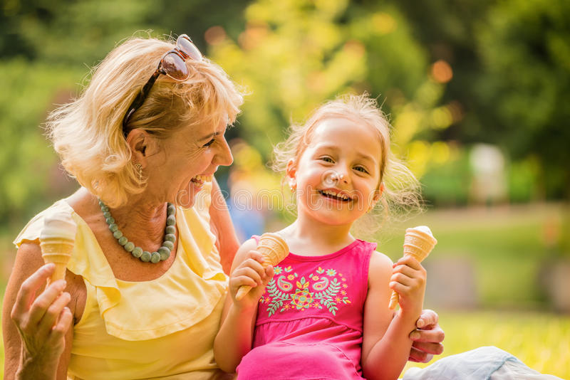 Eating icecream together. Child eating eating icecream together with her grandmother outdoor in nature royalty free stock photography