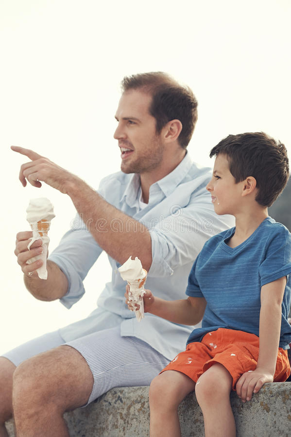 Eating icecream together. Father and son eating icecream together at the beach on vacation having fun with melting mess royalty free stock photography