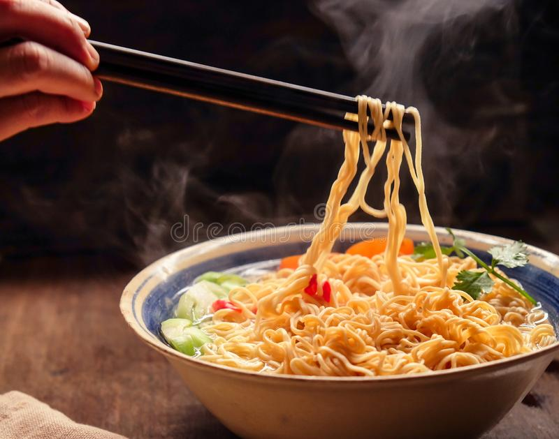 Hand uses chopsticks to pickup tasty noodles with smokes. stock images
