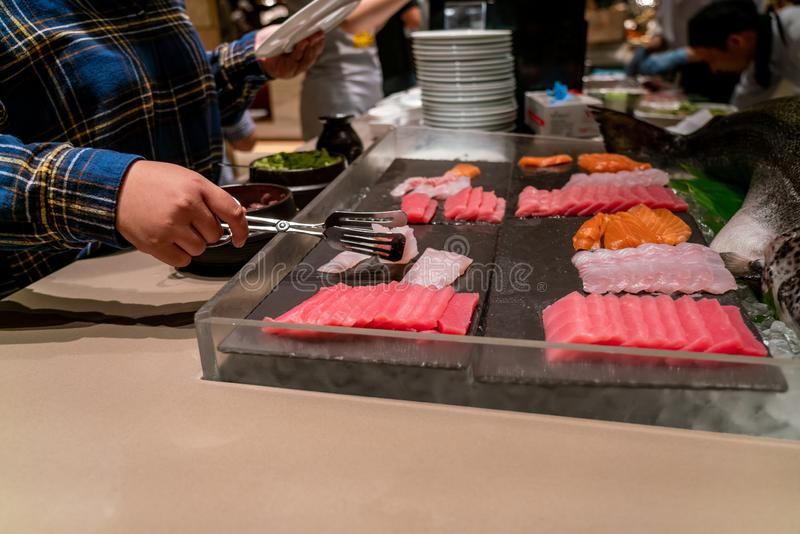 Eating Japanese food with Sashimi, sushi. Side view of young girl eating Japanese food with Sashimi, sushi royalty free stock photography