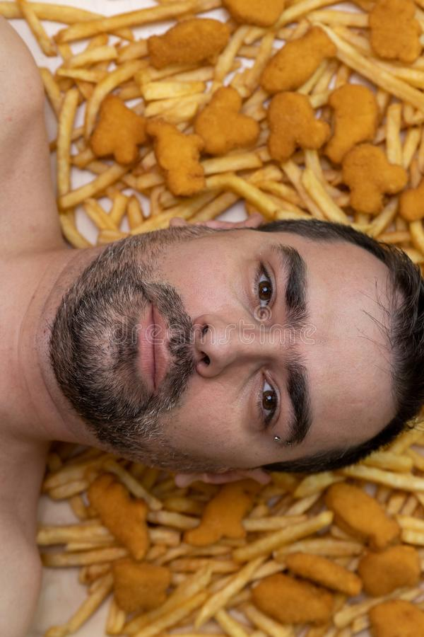 Eating junk food nutrition and dietary health problem concept. Young man laying down surrounded by unhealthy fast food. Diet. Temptation resulting in unhealthy royalty free stock photos
