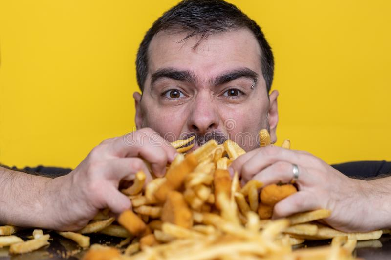 Eating junk food nutrition and dietary health problem concept. Young man eating with two hands a huge amount of unhealthy fast. Food. Diet temptation resulting royalty free stock photos