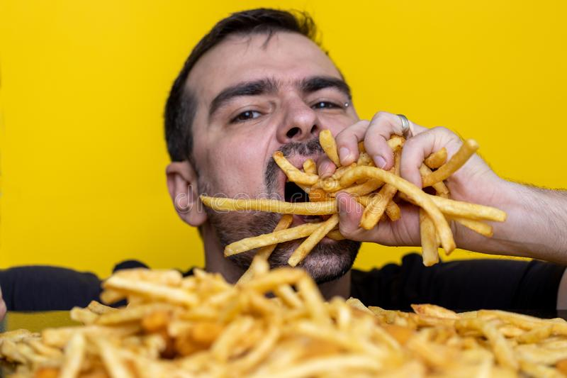 Eating junk food nutrition and dietary health problem concept. Young man eating with two hands a huge amount of unhealthy fast. Food. Diet temptation resulting stock images