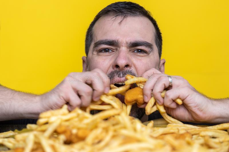 Eating junk food nutrition and dietary health problem concept. Young man eating with two hands a huge amount of unhealthy fast. Food. Diet temptation resulting stock photos