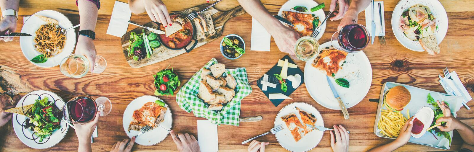 Eating and leisure concept - group of people having dinner at table with food. Family or friends summer party or outdoor dinner. Flat-lay of group of people at stock photos