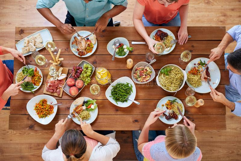Group of people eating at table with food royalty free stock photo