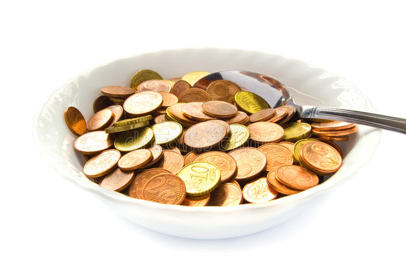 Eating money. A white bowl filled with money. A spoon sticks in the Euro coins. Isolated on white royalty free stock photography