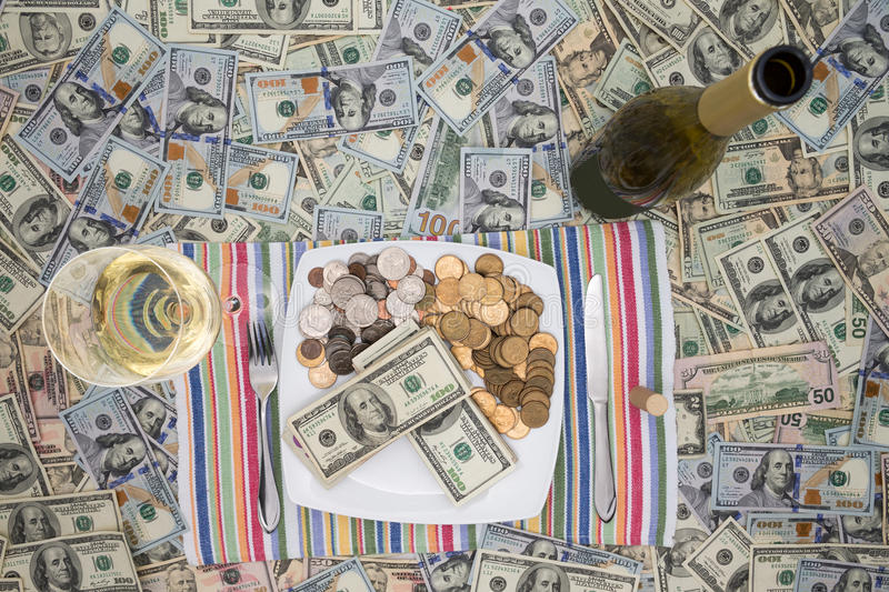 Eating money through greed and extravagance. Conceptual financial image of a plate of money with cutlery flanked by a bottle and glass of champagne on a stock photo