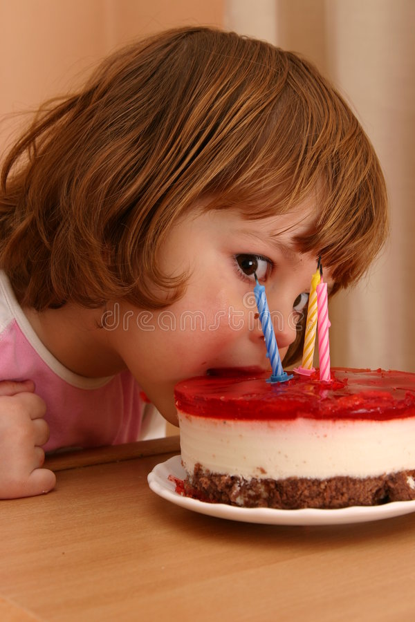 Eating my birthday cake. Little girl taking a mouthful of her birthday cake stock image