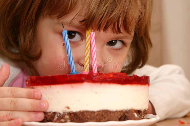 Eating my birthday cake. Little girl taking a mouthful of her birthday cake stock photo