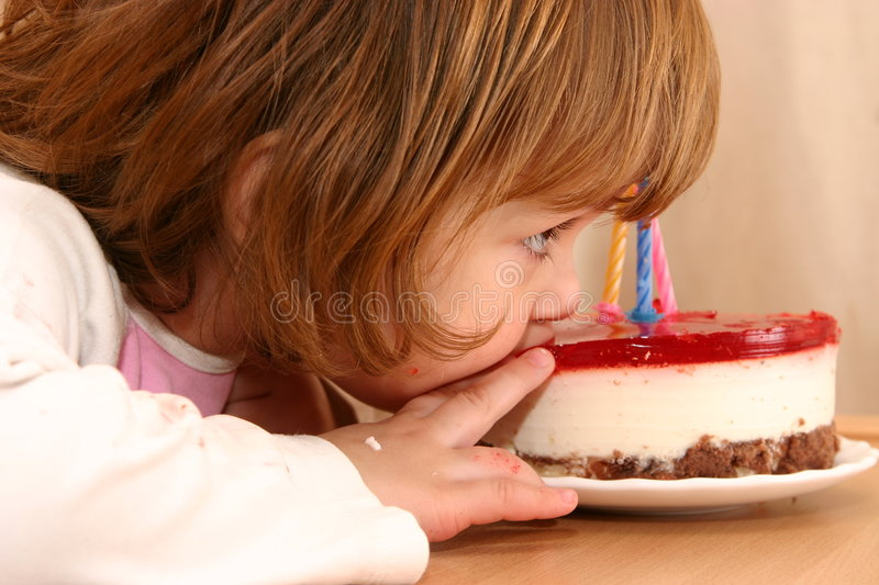 Eating my birthday cake. Little girl taking a mouthful of her birthday cake stock photos