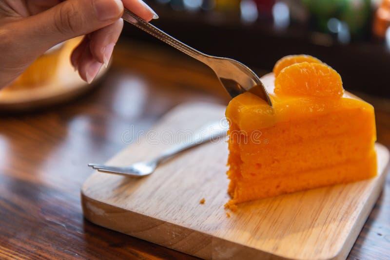 Eating orange cake on wooden table royalty free stock image