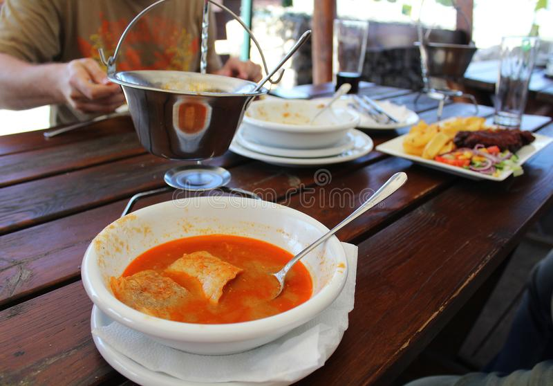 Eating outside - Hungarian fish soup halaszle and invisible eaters royalty free stock images