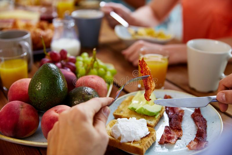 Hands with bacon on fork at table full of food. Eating and people concept - male hands with knife and bacon on fork at table full of food stock images