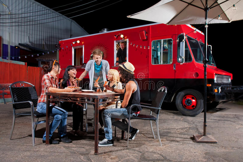 Eating Pizza Near Food Truck. Laughing friends at food truck eating pizza slices stock photo