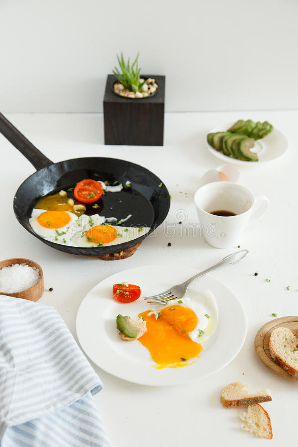 Eating in the process, fried eggs in a frying pan and on a plate, toast with avocado and a cup of coffee for breakfast. stock images