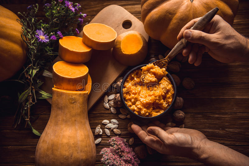 Eating pumpkin millet porridge with milk, hands, breakfast on a wooden background royalty free stock images
