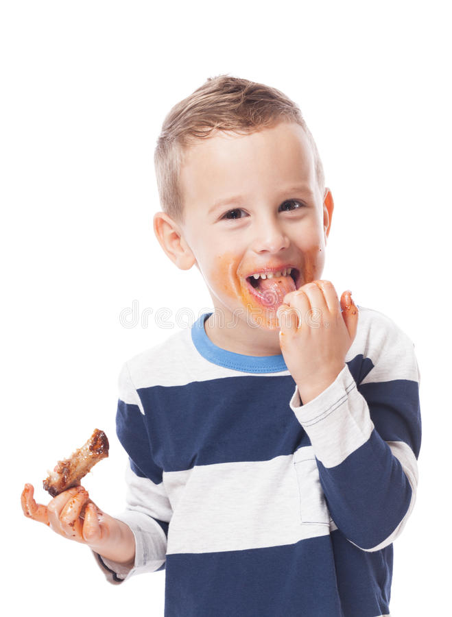 Eating ribs. Adorable kid eating bbq ribs on isolated white stock image