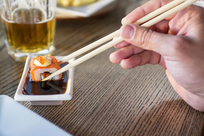 Eating roll sushi in japanese restaurant, hand with chopsticks closeup royalty free stock image