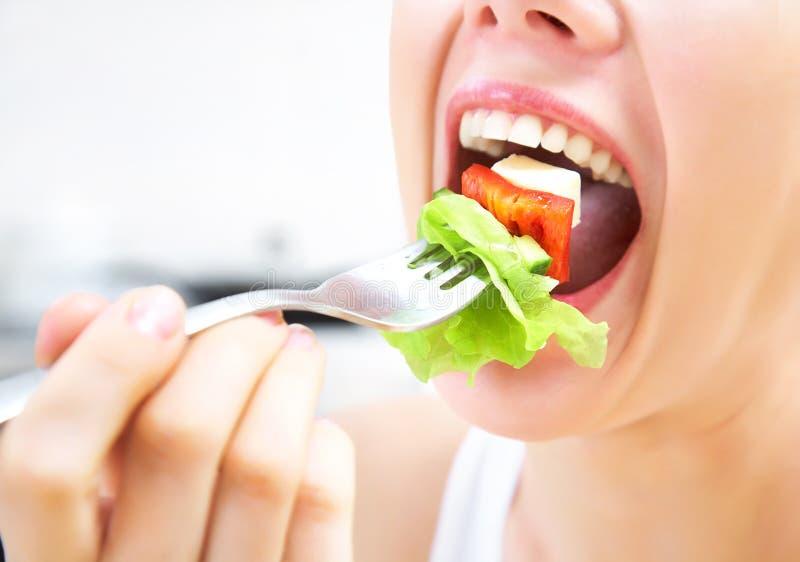Eating salad. Close-up of woman eating fresh salad royalty free stock photos