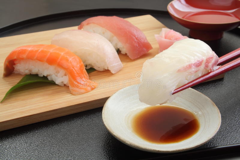 Eating Sea Bream Sushi with Chopsticks and Sake, Japanese Food. A dish of assorted sushi: sea bream, salmon, Japanese amber jack, tuna 4 kinds with soy sauce royalty free stock photography