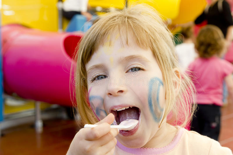 Eating spoon funny girl playground smiling blond royalty free stock photography