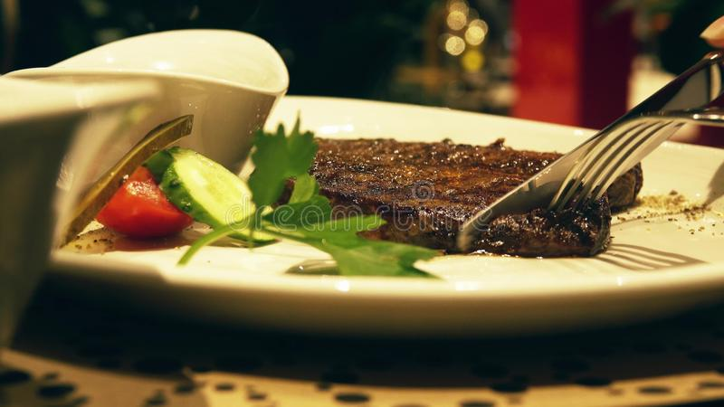 Eating juicy steaming steak in a restaurant, plate close-up shot royalty free stock photos